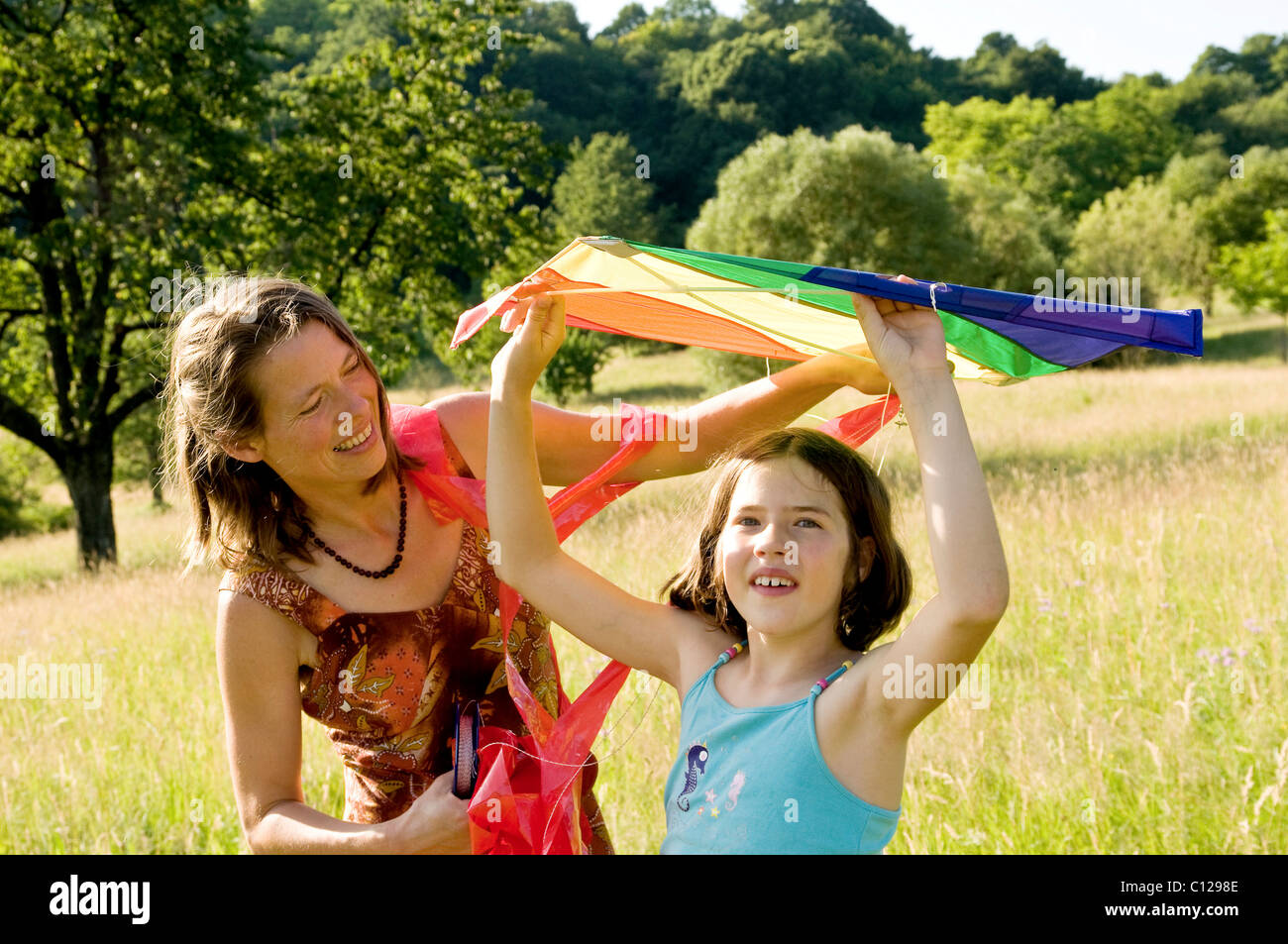 Mother and child with a kite in a summer meadow in the Black Forest, Baden-Wuerttemberg, Germany, Europe - Stock Image