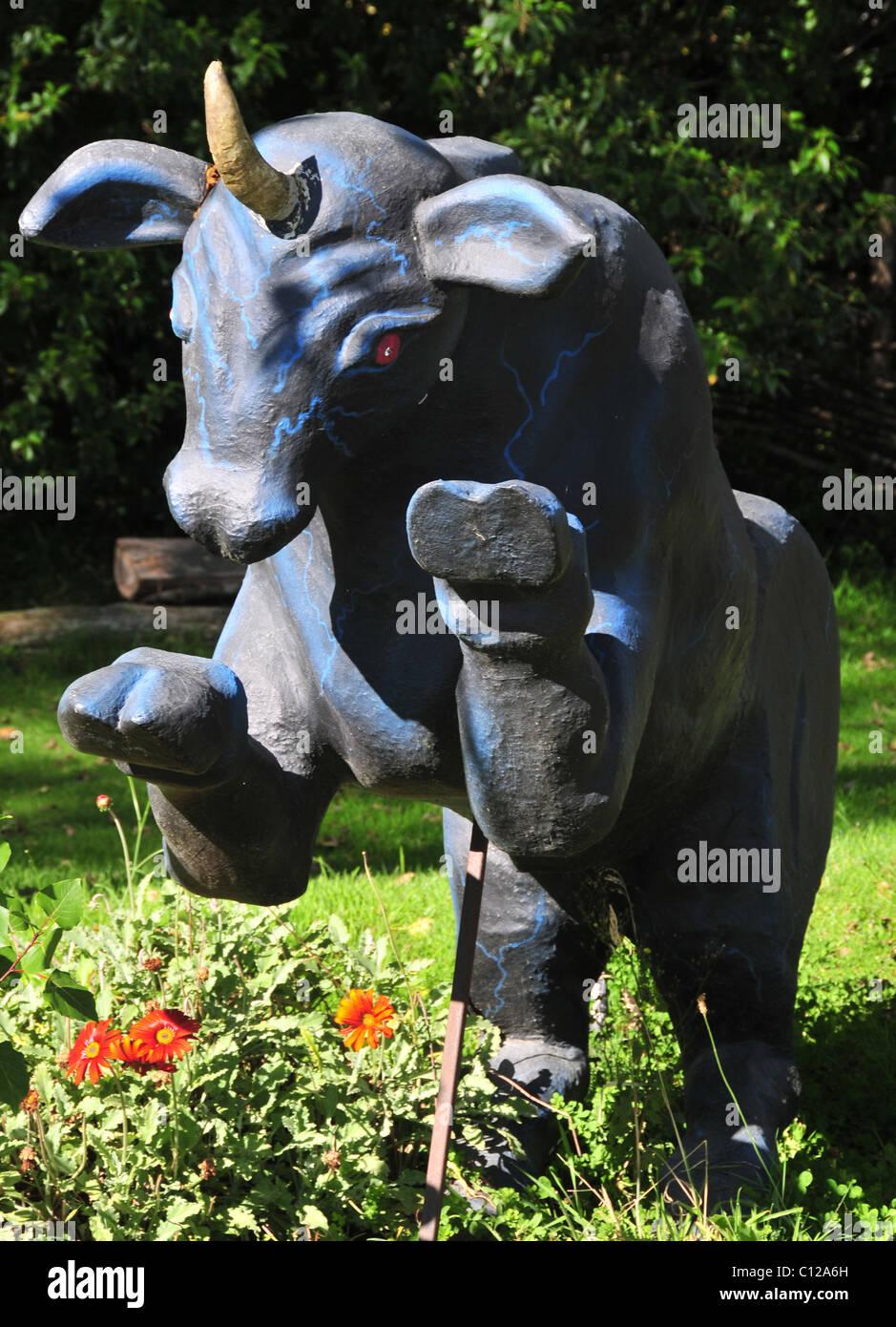 Sunny  portrait of a mythical blue bull-unicorn Camahueto effigy rearing above red garden flowers, Caulin, Chiloe Stock Photo