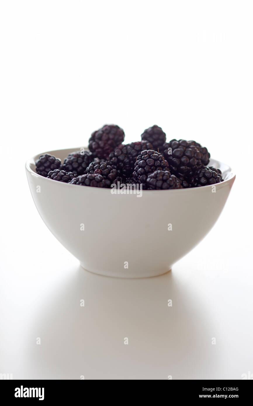 White bowl of blackberries on white - Stock Image