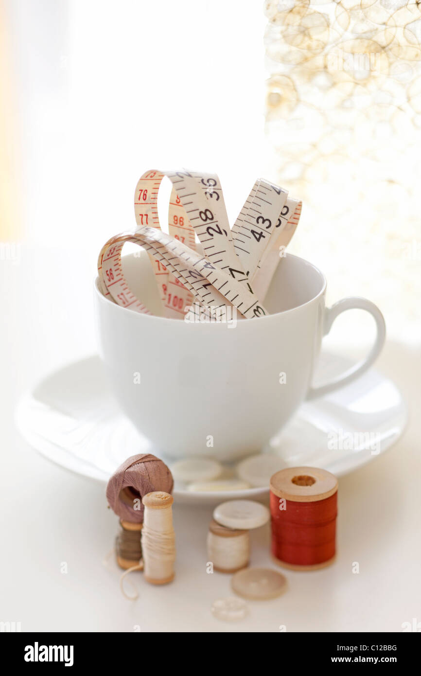 tea cup holding measuring tape and thread and sewing items - Stock Image