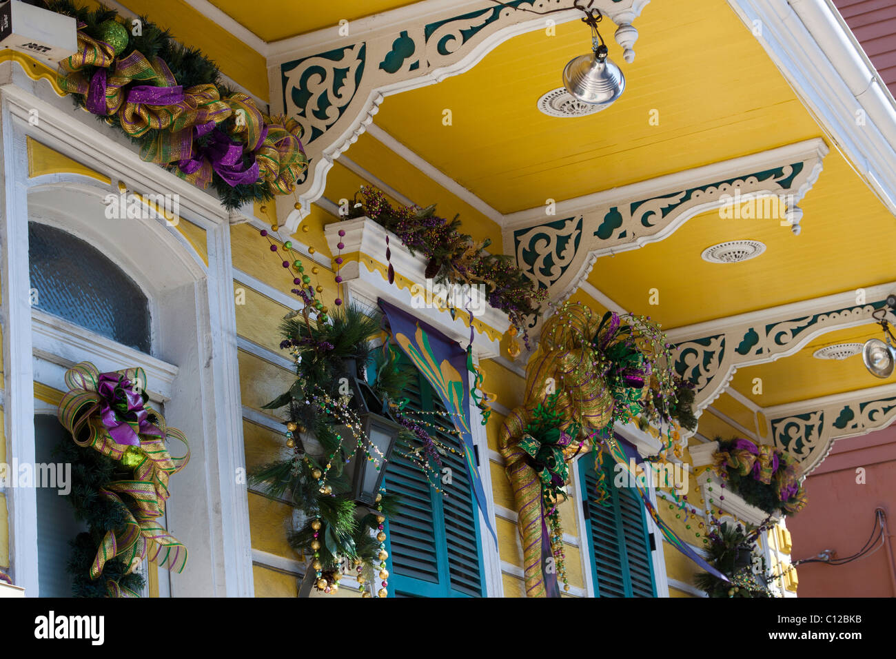 Closeup of decorative corbels with windows decorated for Mardi Gras on a Creole townhouse in the French Quarter - Stock Image
