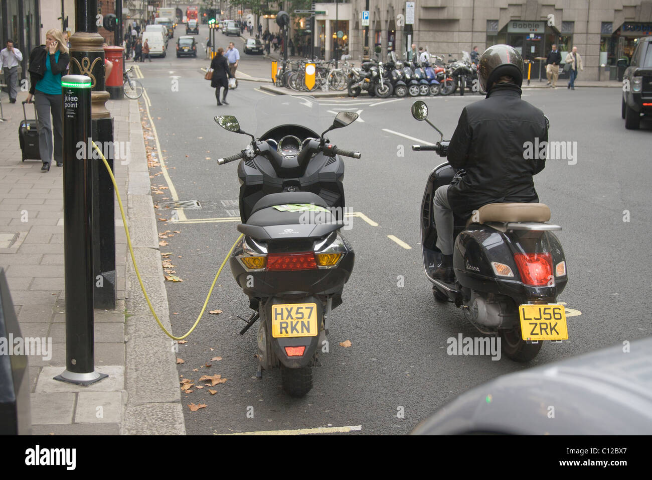 An electric motorbike being  re-charged , London , UK. - Stock Image