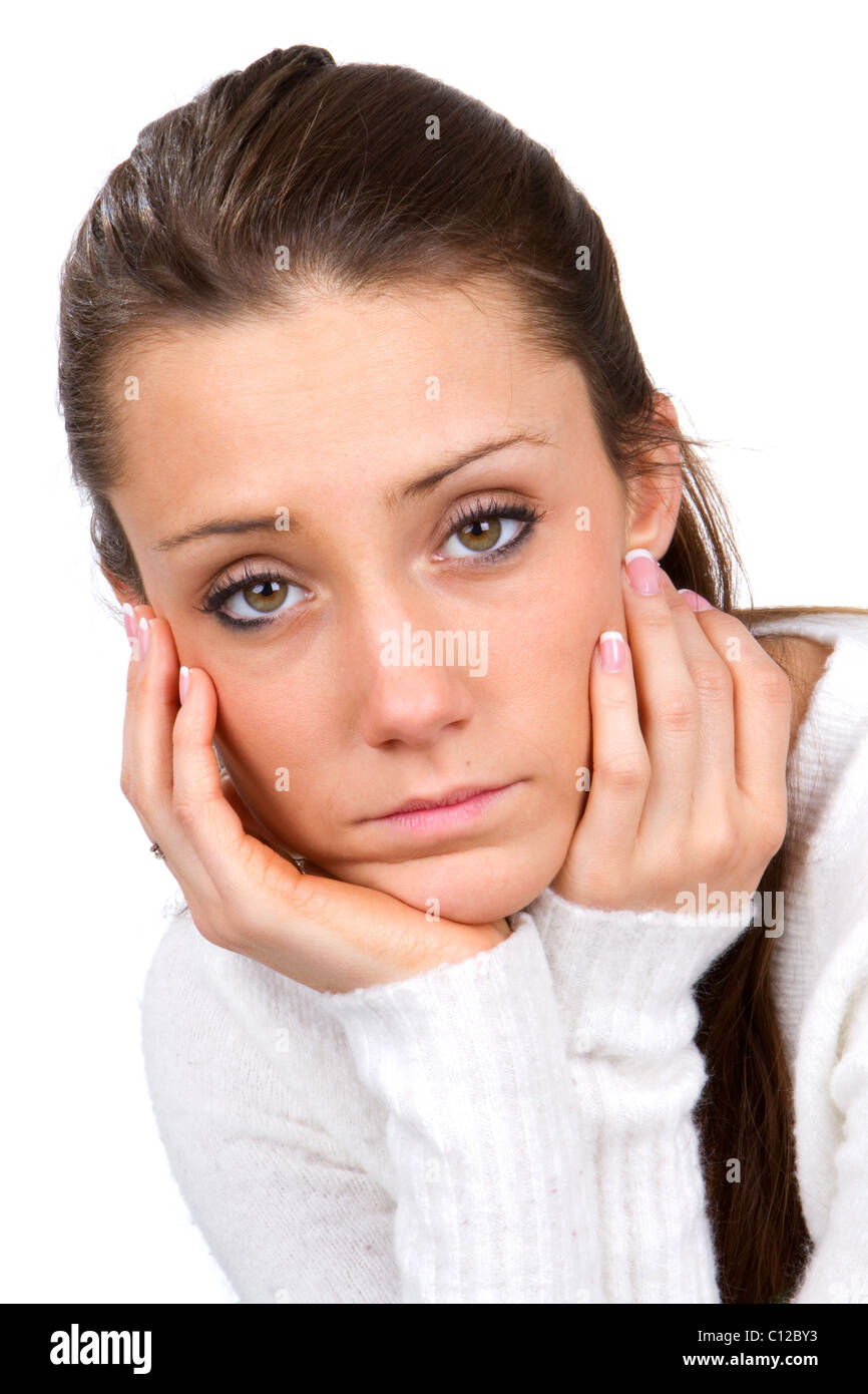Sad faced young woman holds her face in her hands. Stock Photo