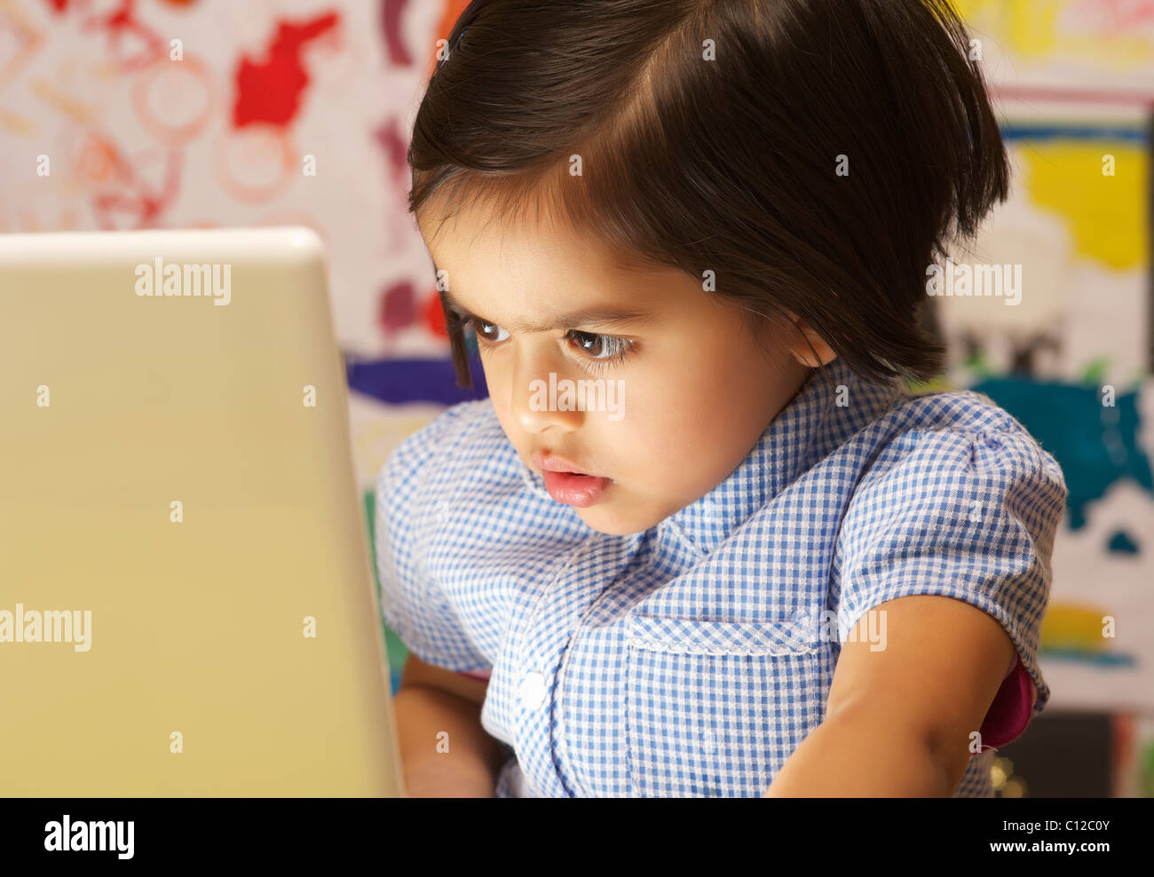 A young school girl looking at a laptop computer uk - Stock Image