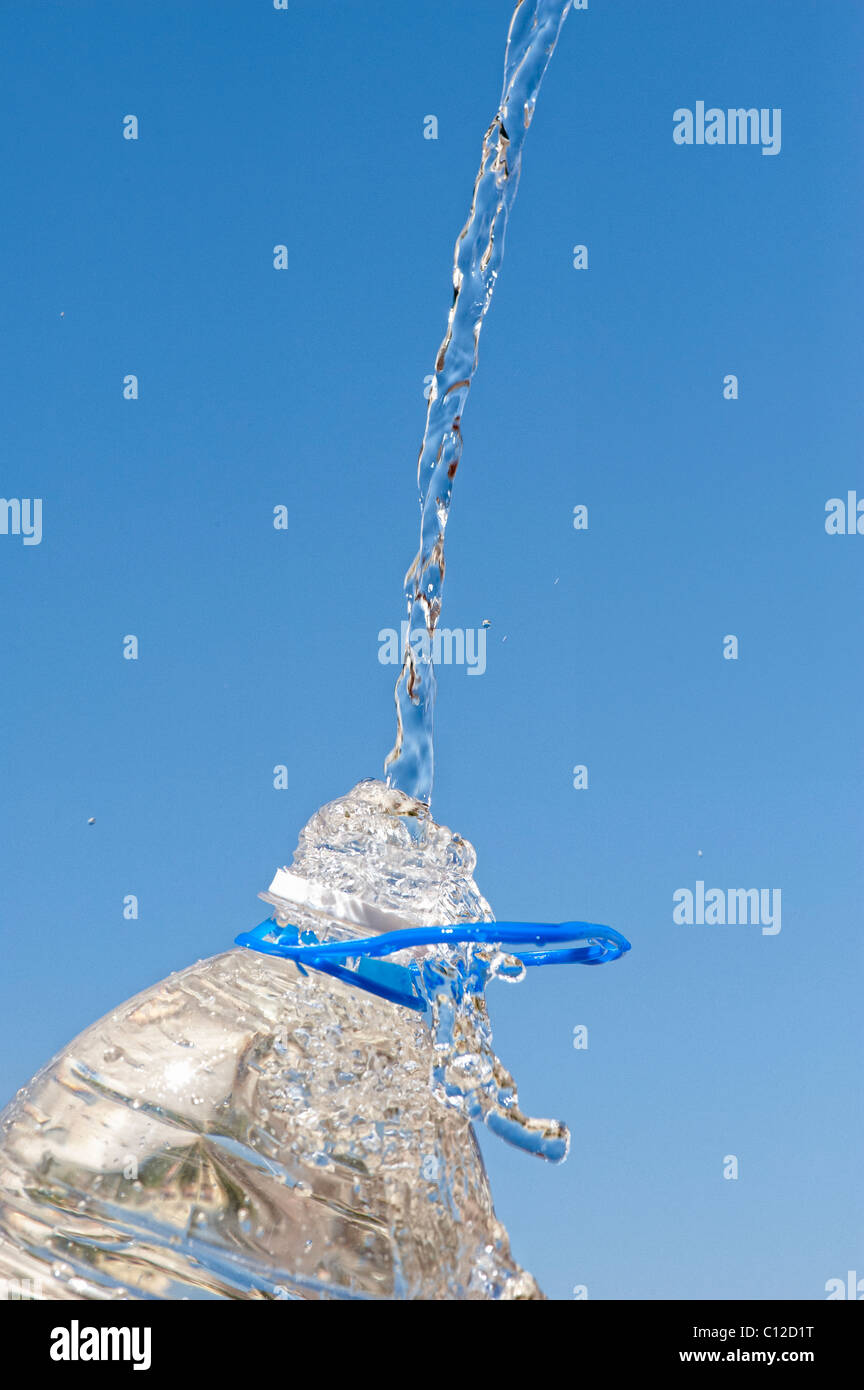 Pouring water into a plastic mineral water bottle against a blue sky - Stock Image