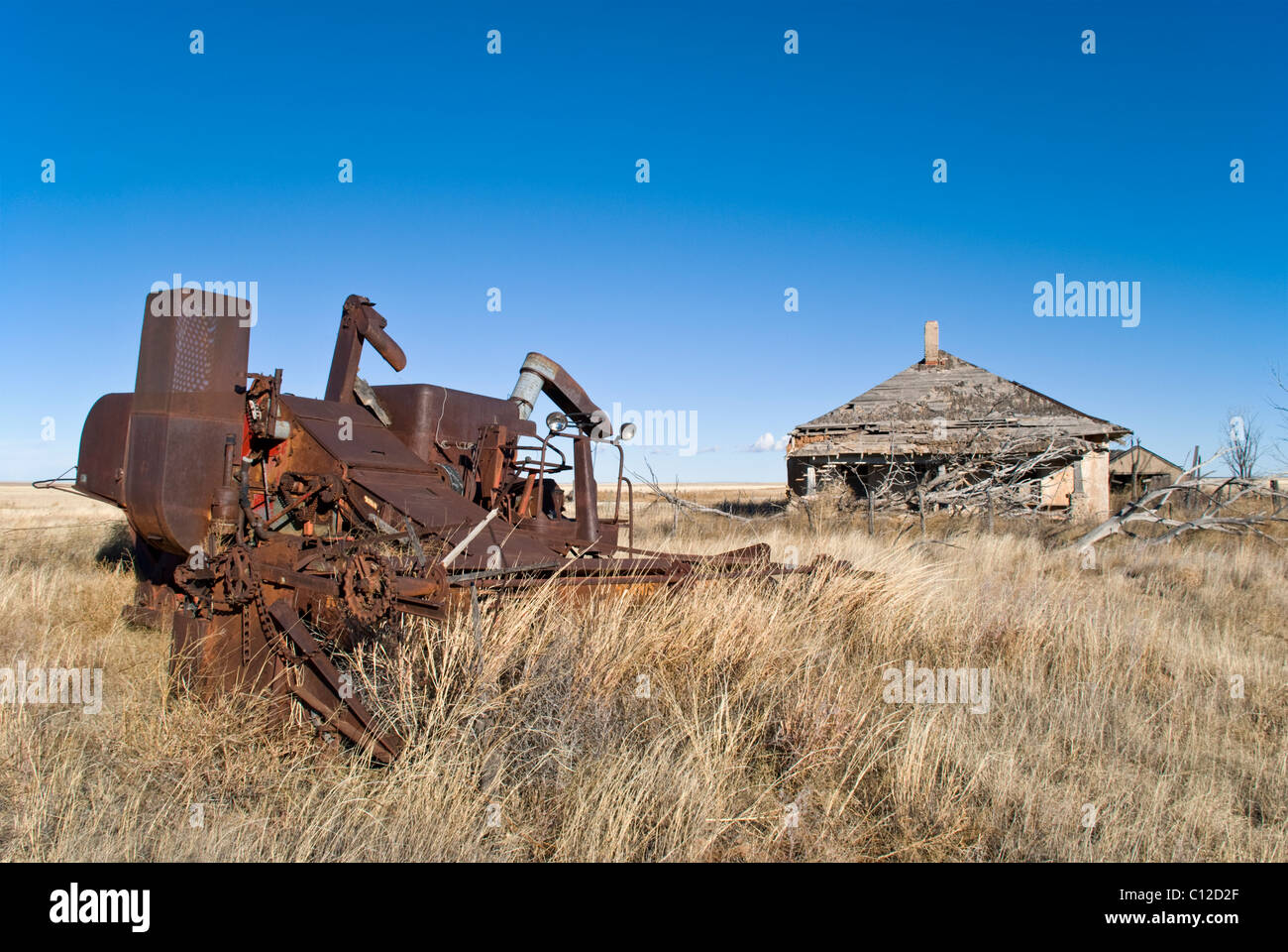 Rusty old farm machinery sits in front of an abandoned house in Quay County, New Mexico. - Stock Image