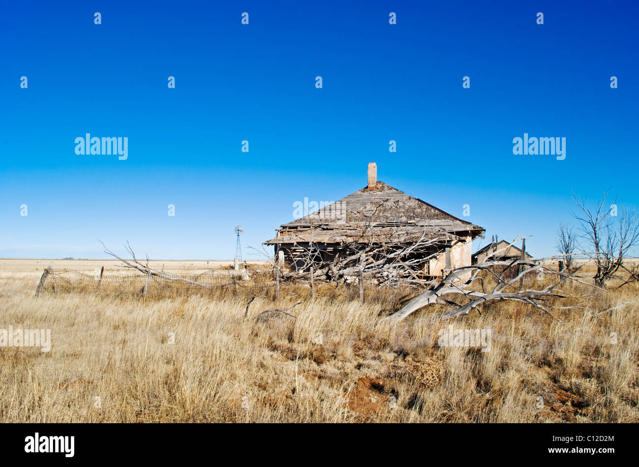 A distant windmill and deserted homestead echoes a more vibrant past in this northeastern portion of New Mexico. - Stock Image