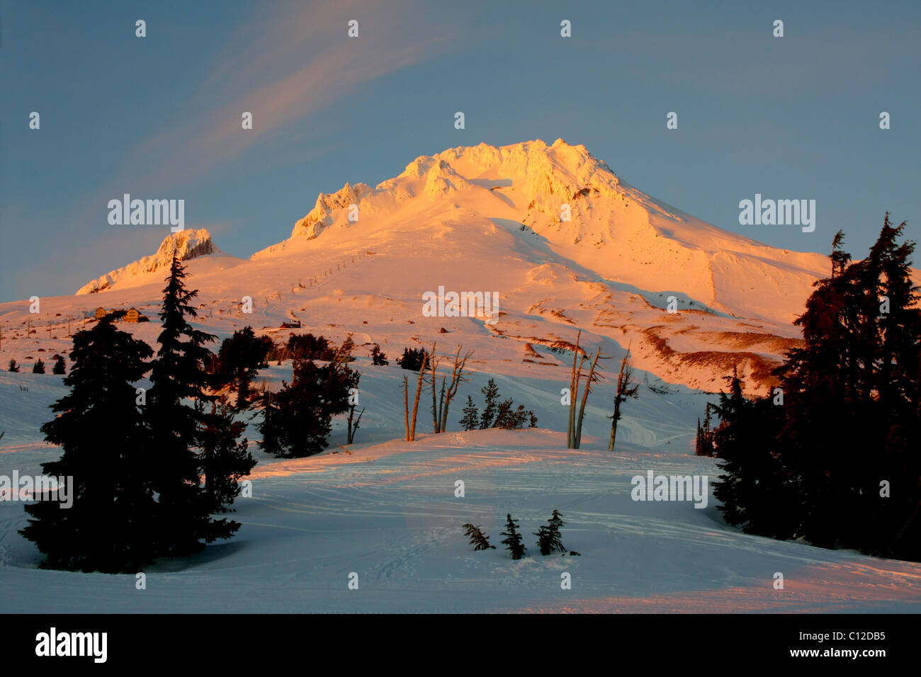 40,171.06371a A snowy jagged topped mountain peak with a bright yellowish glow in a white winter sunset against - Stock Image