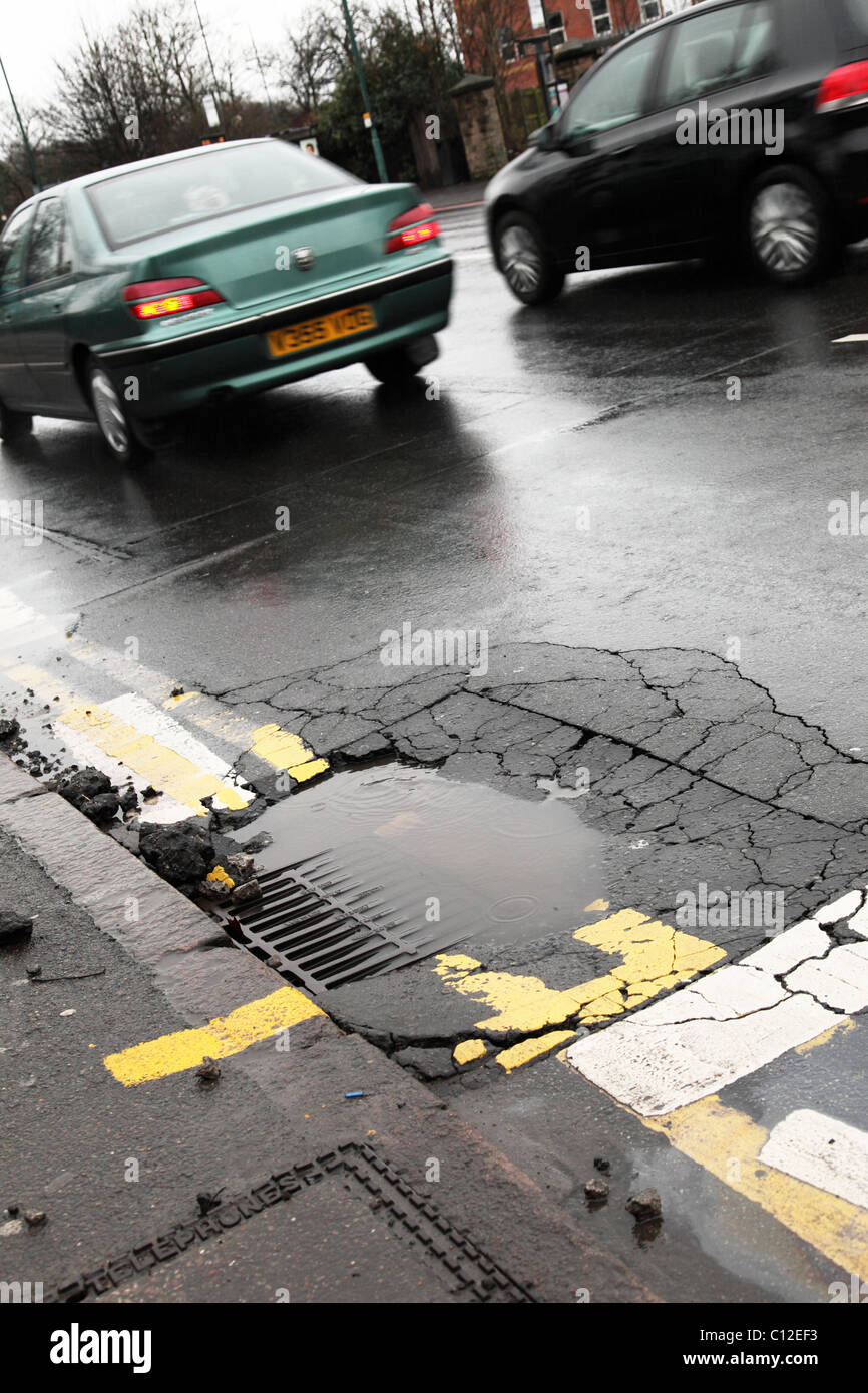 Potholes on a road in a U.K. city. - Stock Image