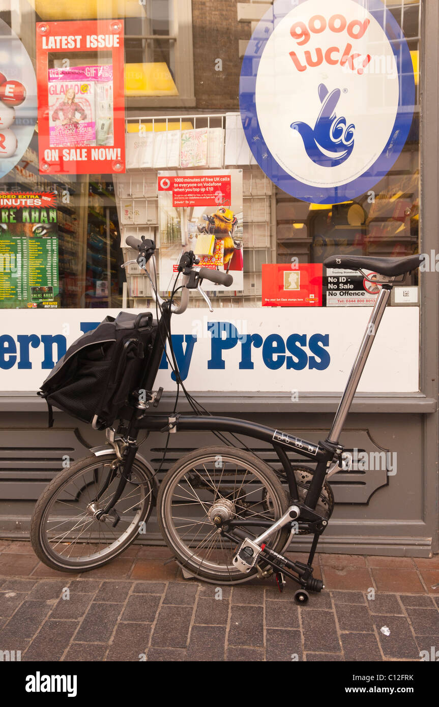 A Brompton fold away bicycle folded up outside a Uk shop - Stock Image