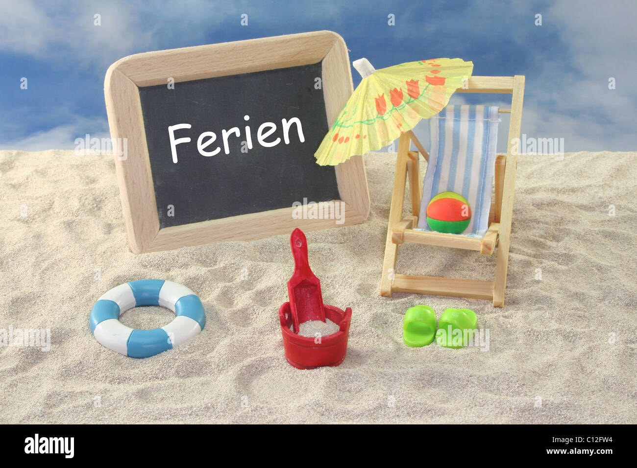 School board and toys on a sandy beach Stock Photo