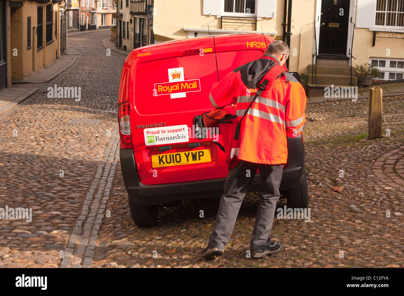 A Royal Mail postman delivering mail in Elm hill in Norwich , Norfolk , England , Britain , Uk - Stock Image