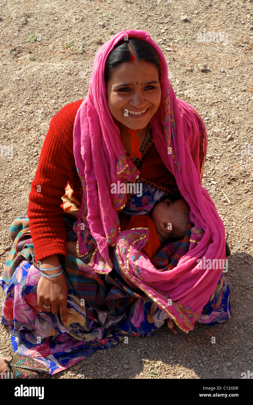 Young Rajasthani girl breast feeding her baby in desert while on a rest  from work