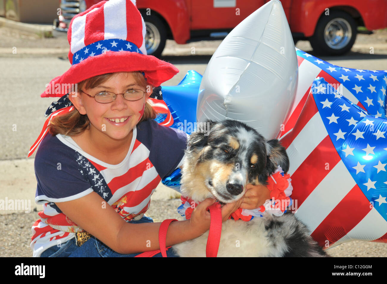 A patriotic young girl and her blind dog are in the 4th of July parade in Capitan, New Mexico. - Stock Image