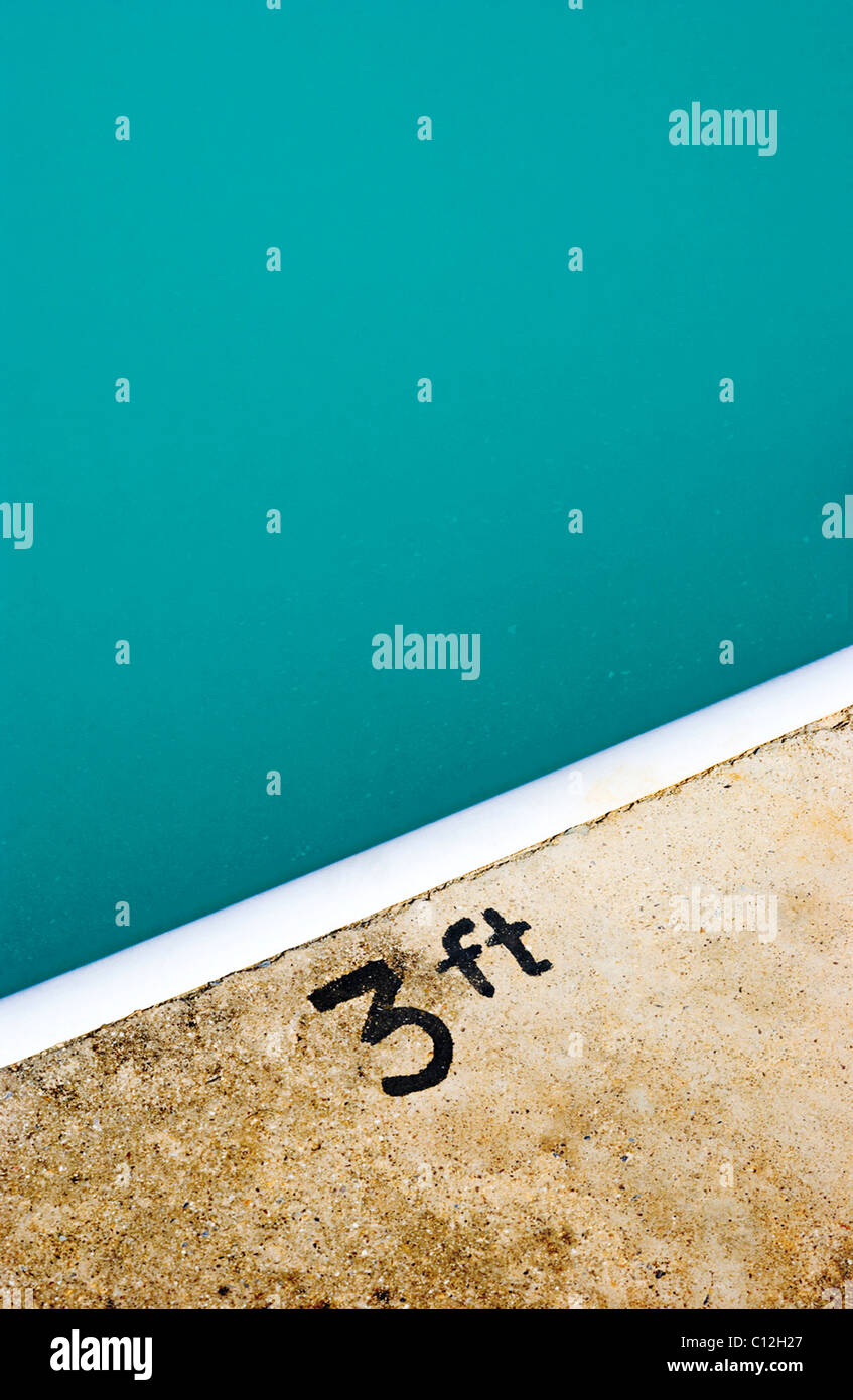 A swimming pool with a 3ft sign painted on the edge of the pool. - Stock Image