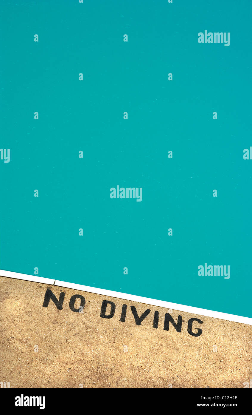A swimming pool with a no diving sign painted on the edge of the pool. - Stock Image