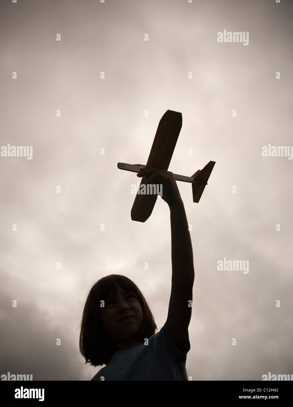 A ten year old girl holds a toy balsa wood plane as she is silhouetted against a dark and cloudy sky. - Stock Image