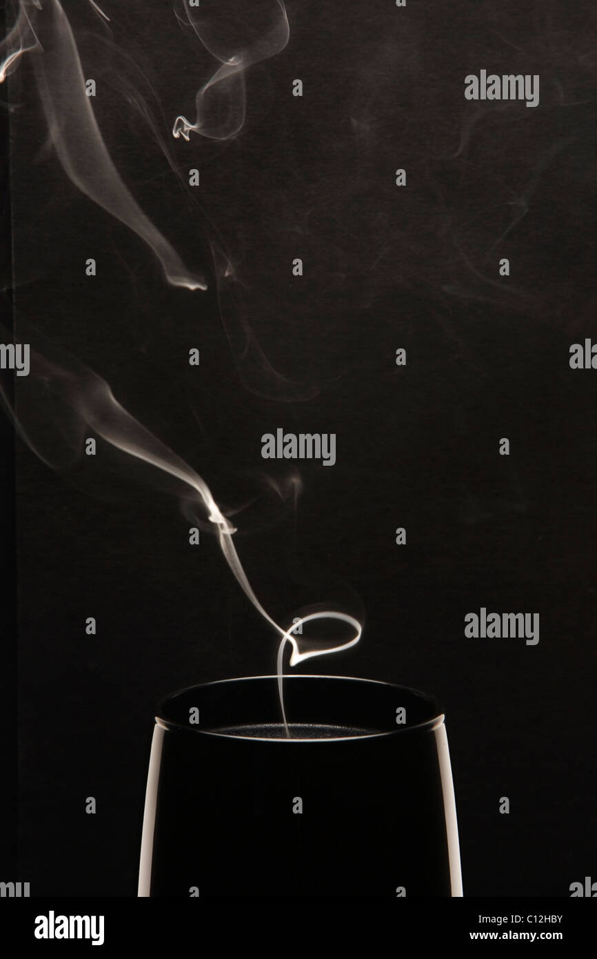 White smoke rising from a black candle against a black background. - Stock Image