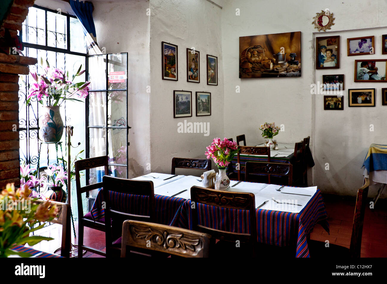 beautiful light filled rustic interior of Oaxacan home style restaurant with family photos on wall in Oaxaca City - Stock Image