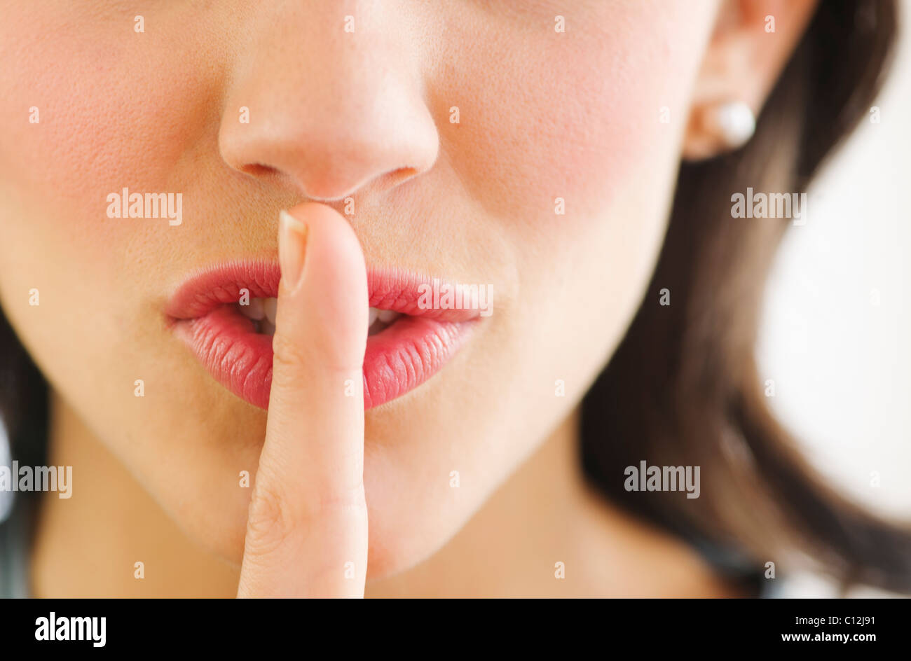 Young woman with finger on lips, close-up - Stock Image