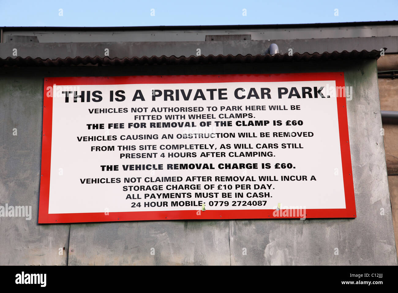 A wheel clamping warning sign in a private car park in a U.K. city. - Stock Image