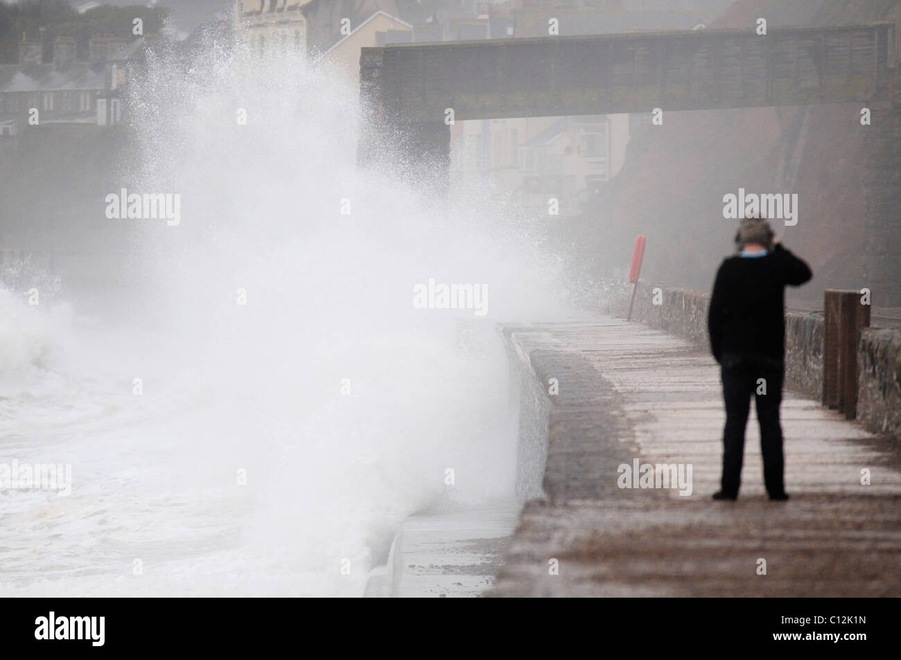 Young man taking photos of the sea splashing up against the sea wall at Dawlish in Devon - Stock Image