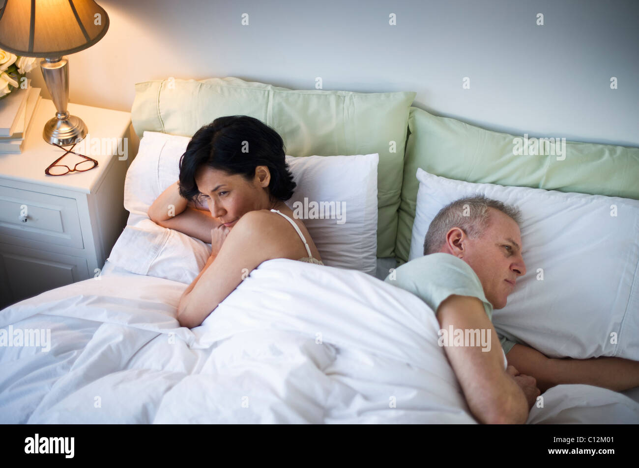 USA, New Jersey, Jersey City, Mature couple laying in bed after argument - Stock Image