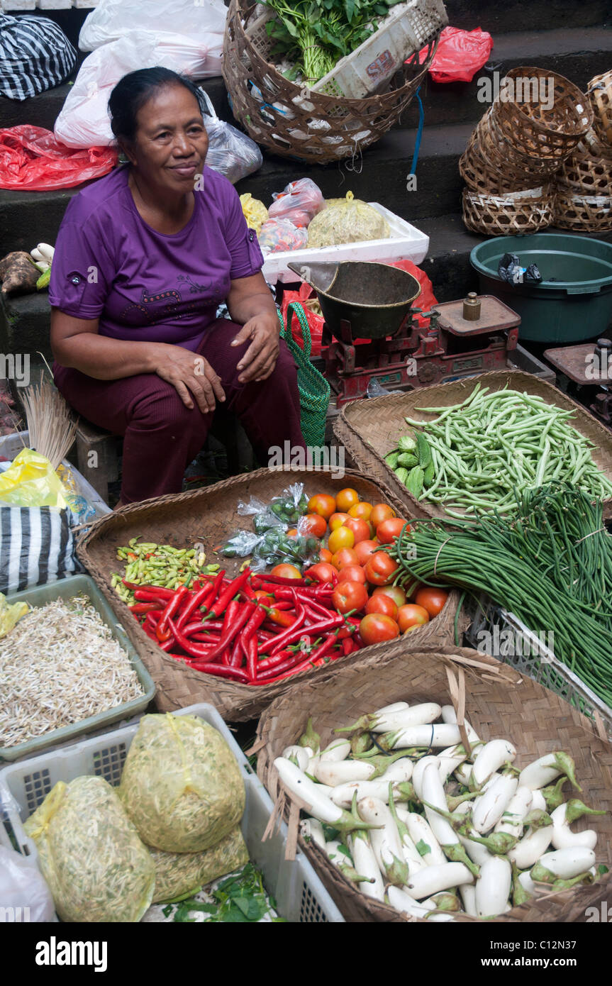 Balinese woamn sitting with her wares in the market in Ubud, Bali, Indonesia - Stock Image