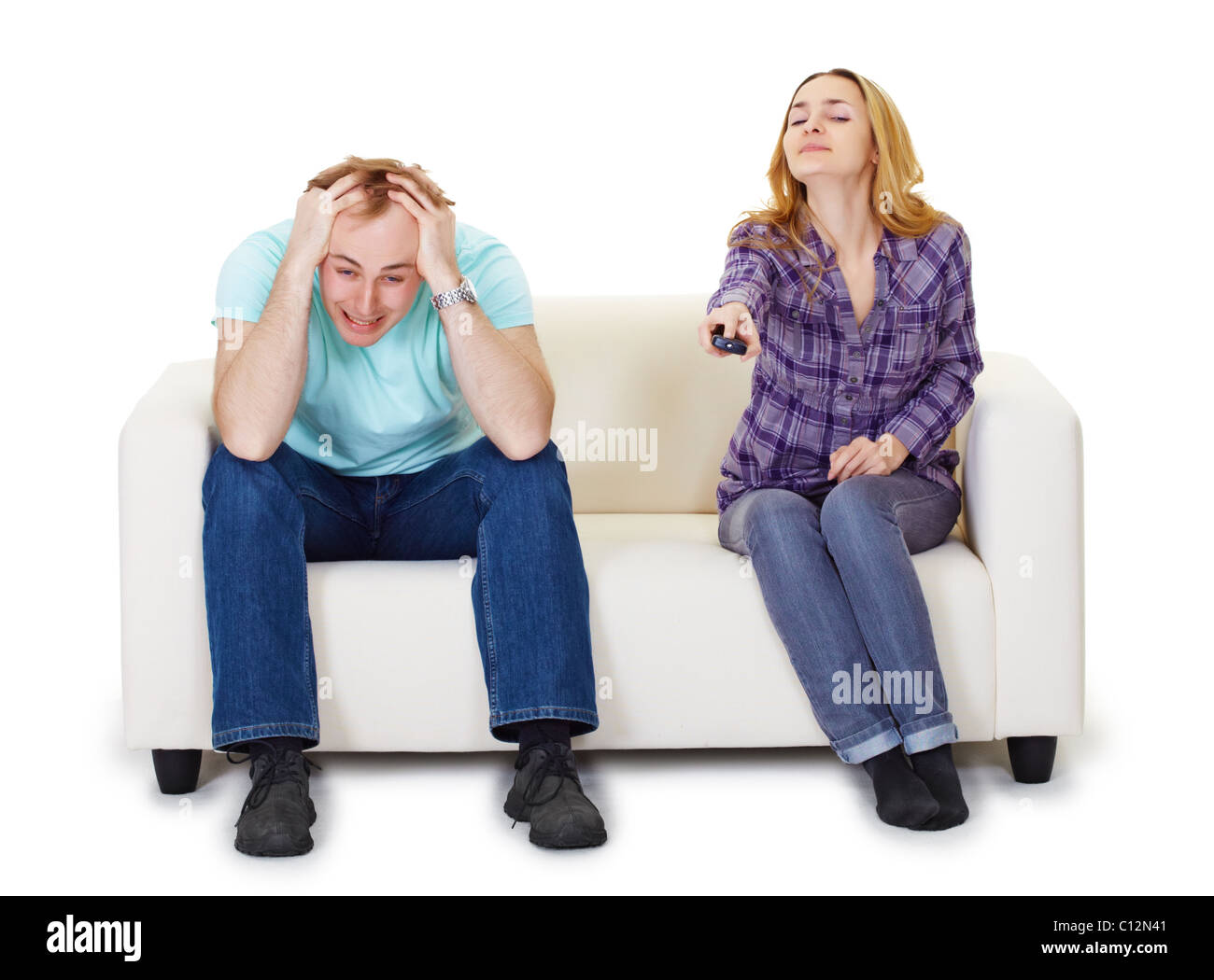 Nervous husband and wife sitting on the couch watching TV isolated on white background - Stock Image