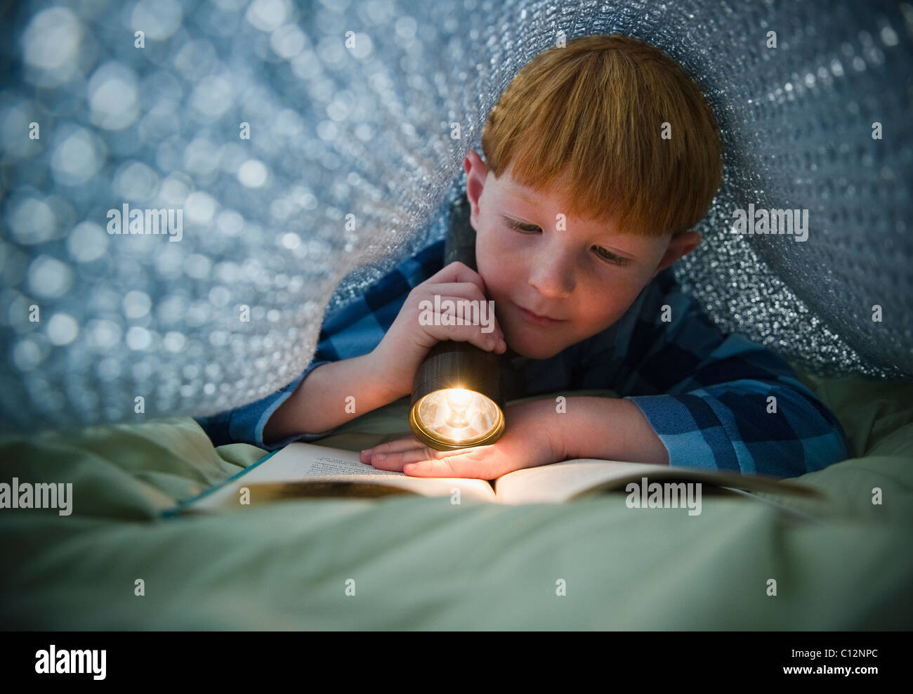 USA, New Jersey, Jersey City, Boy (8-9) reading book under bed covers - Stock Image