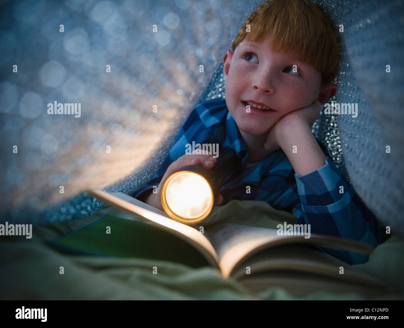 USA, New Jersey, Jersey City, Boy (8-9) reading book under bed covers Stock Photo