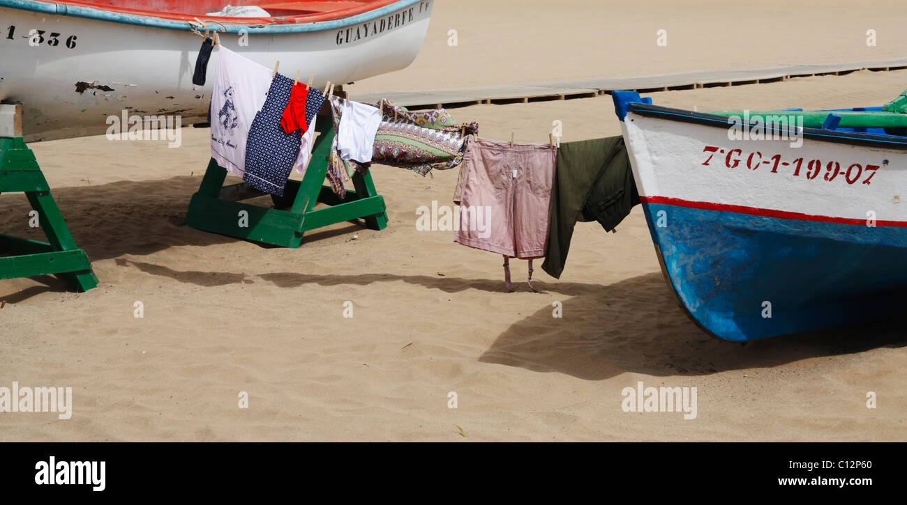 Washing on line tied between two boats on beach in Spain - Stock Image