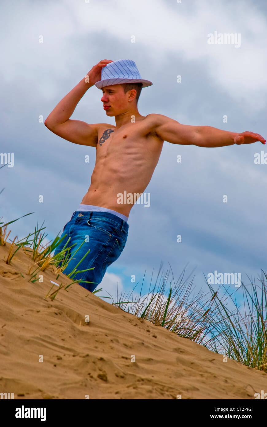 Barechested young man stands with hand on head on a sand dune - Stock Image