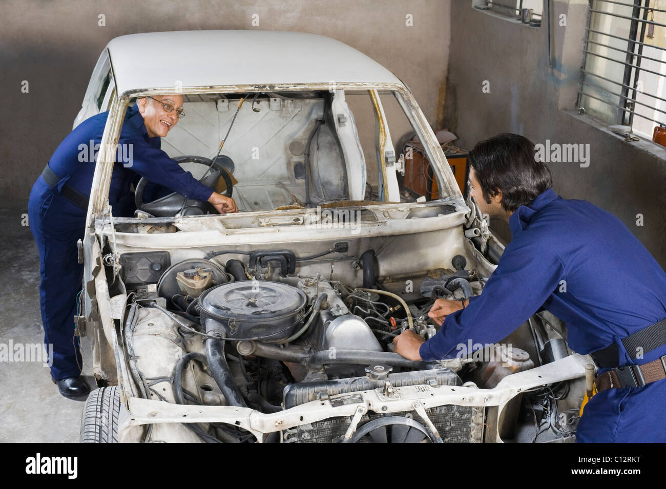 Auto mechanic with an apprentice repairing a car in a garage - Stock Image