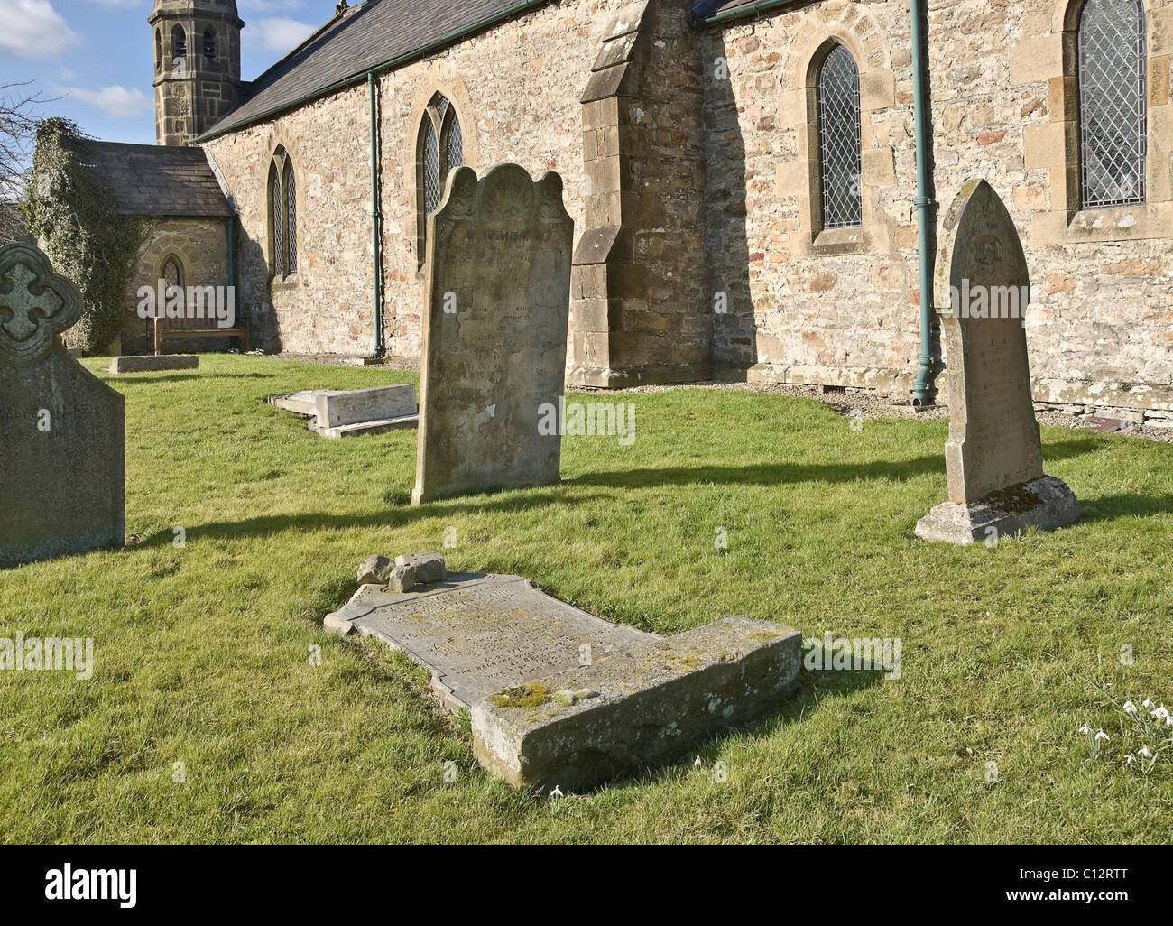 Grave stone flattened in the name of safety. Bellerby churchyard in North Yorkshire. - Stock Image