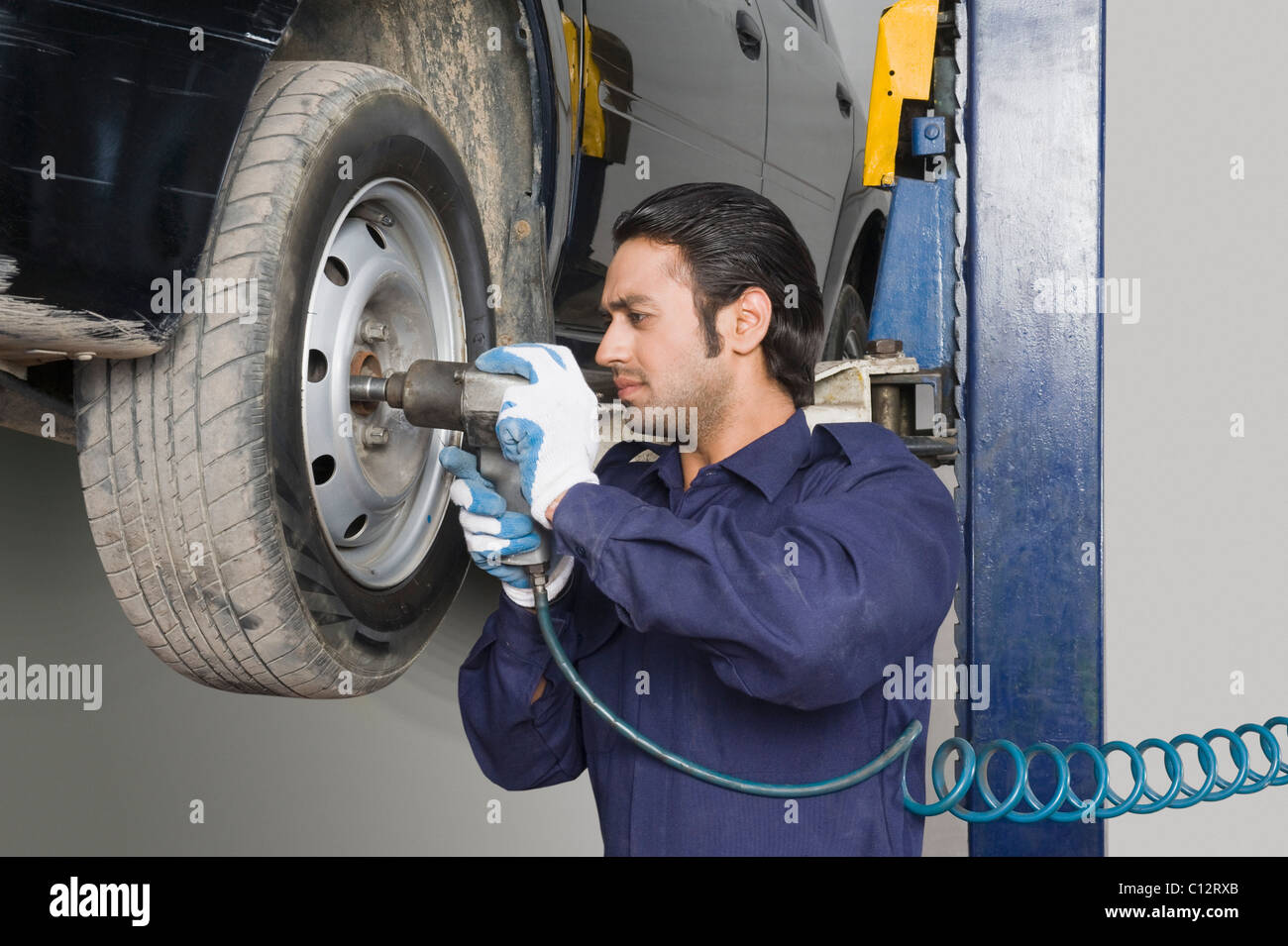 Auto mechanic fixing tire with a power tool - Stock Image