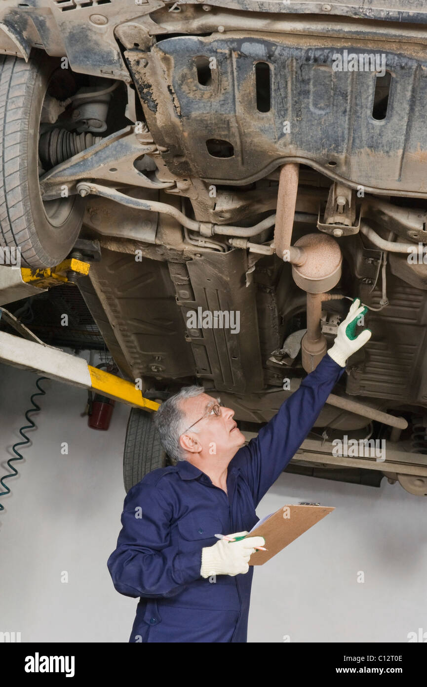 Auto mechanic working under a raised car in a garage - Stock Image