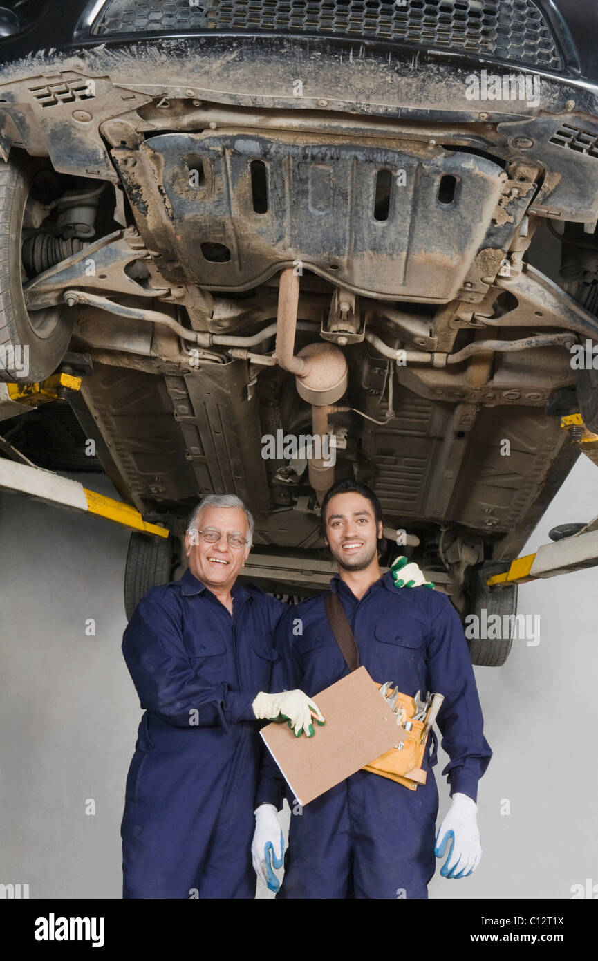Auto mechanic with an apprentice standing under a raised car in a garage - Stock Image