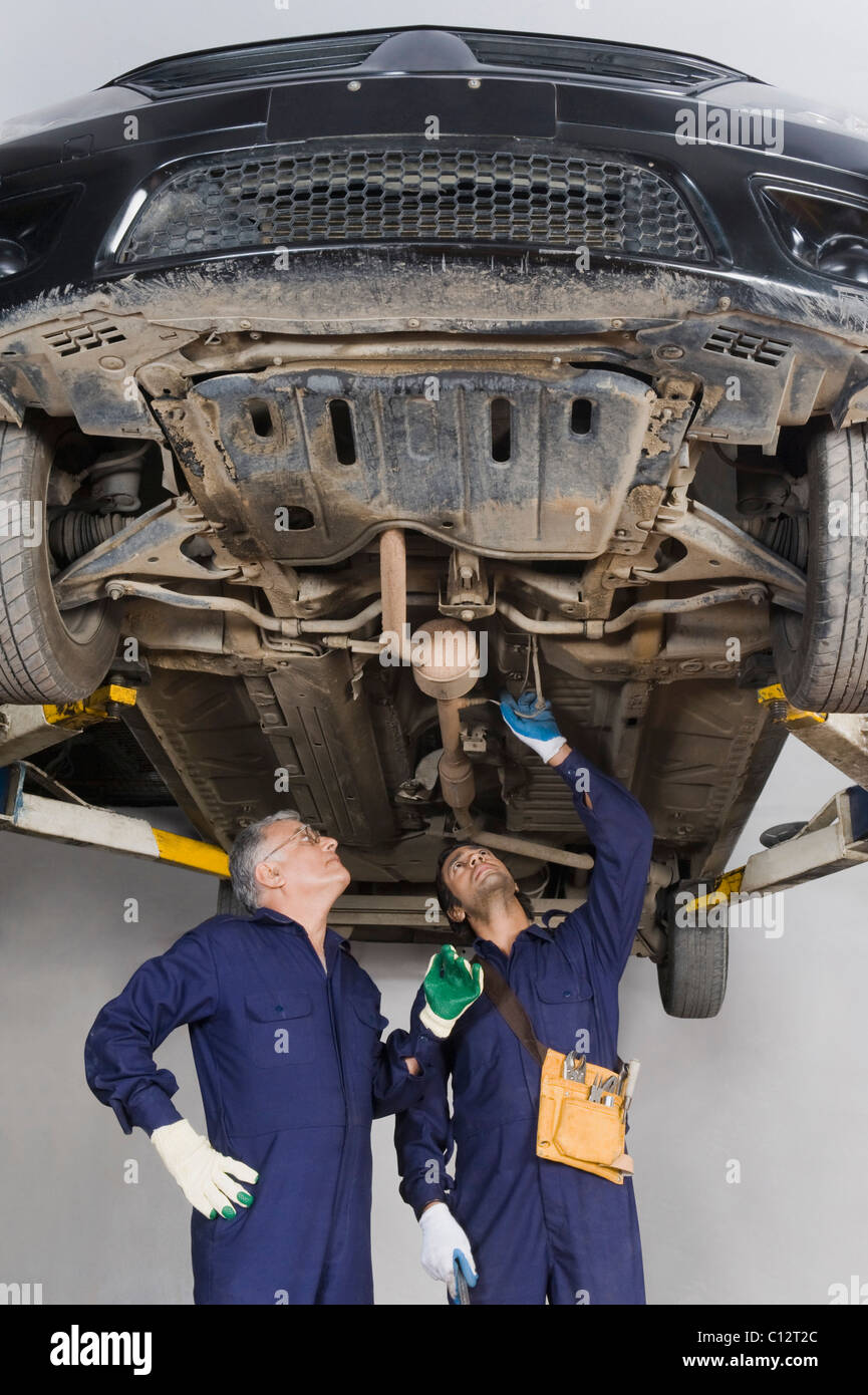 Auto mechanic with an apprentice working under a raised car in a garage - Stock Image