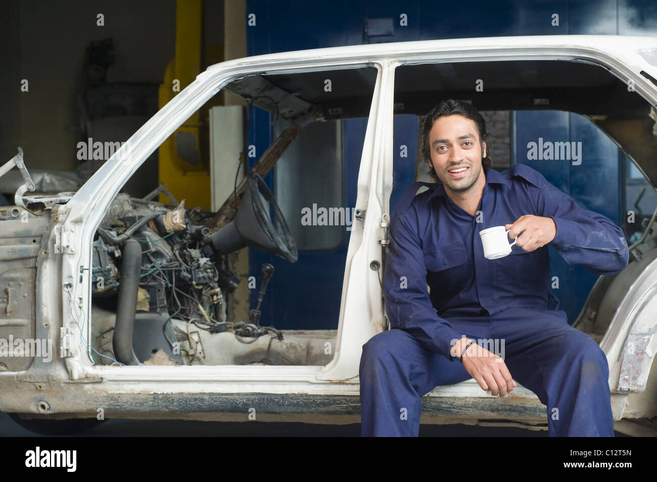 Portrait of an auto mechanic drinking coffee in a garage - Stock Image