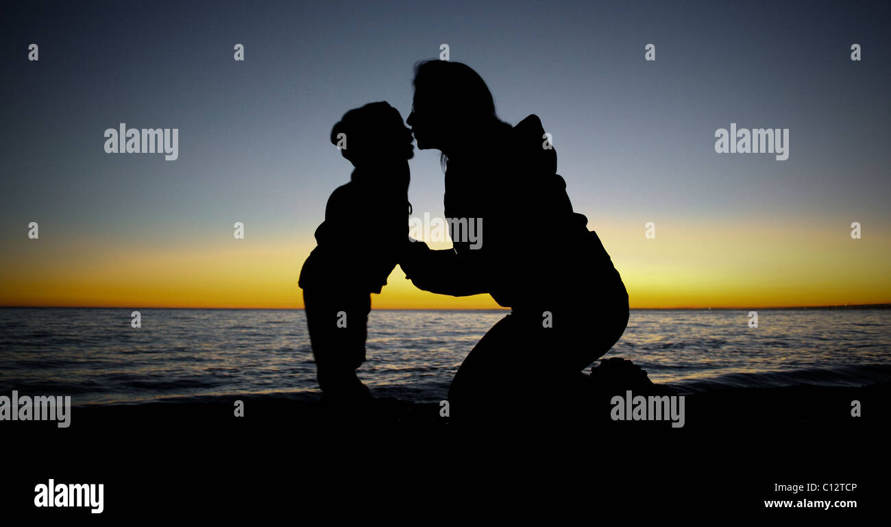 Mother kneels kissing child at waters edge, sunset Stock Photo