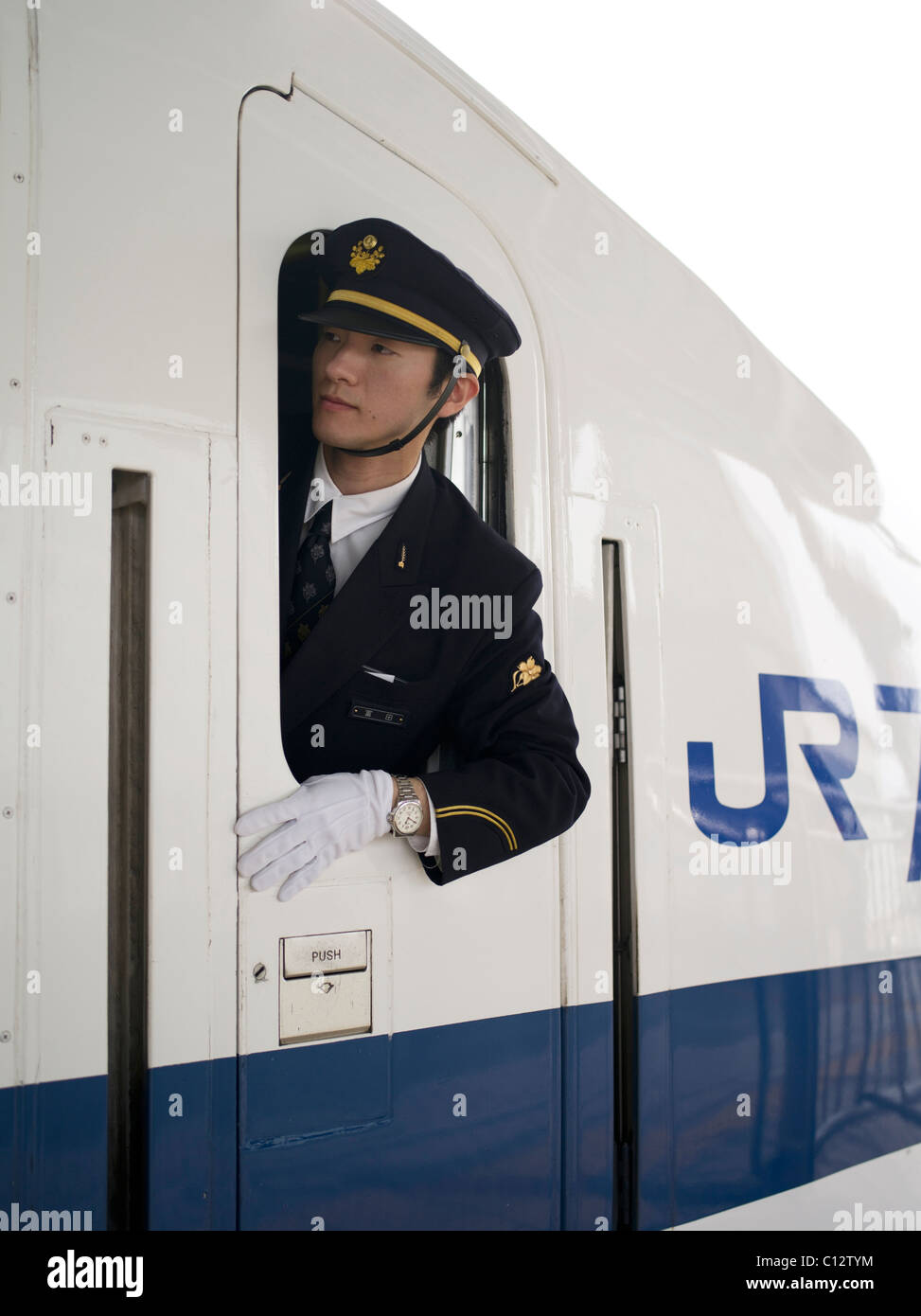Shinkansen Bullet train conductor checks the platform as the train pulls out of Osaka station bound for Tokyo. - Stock Image