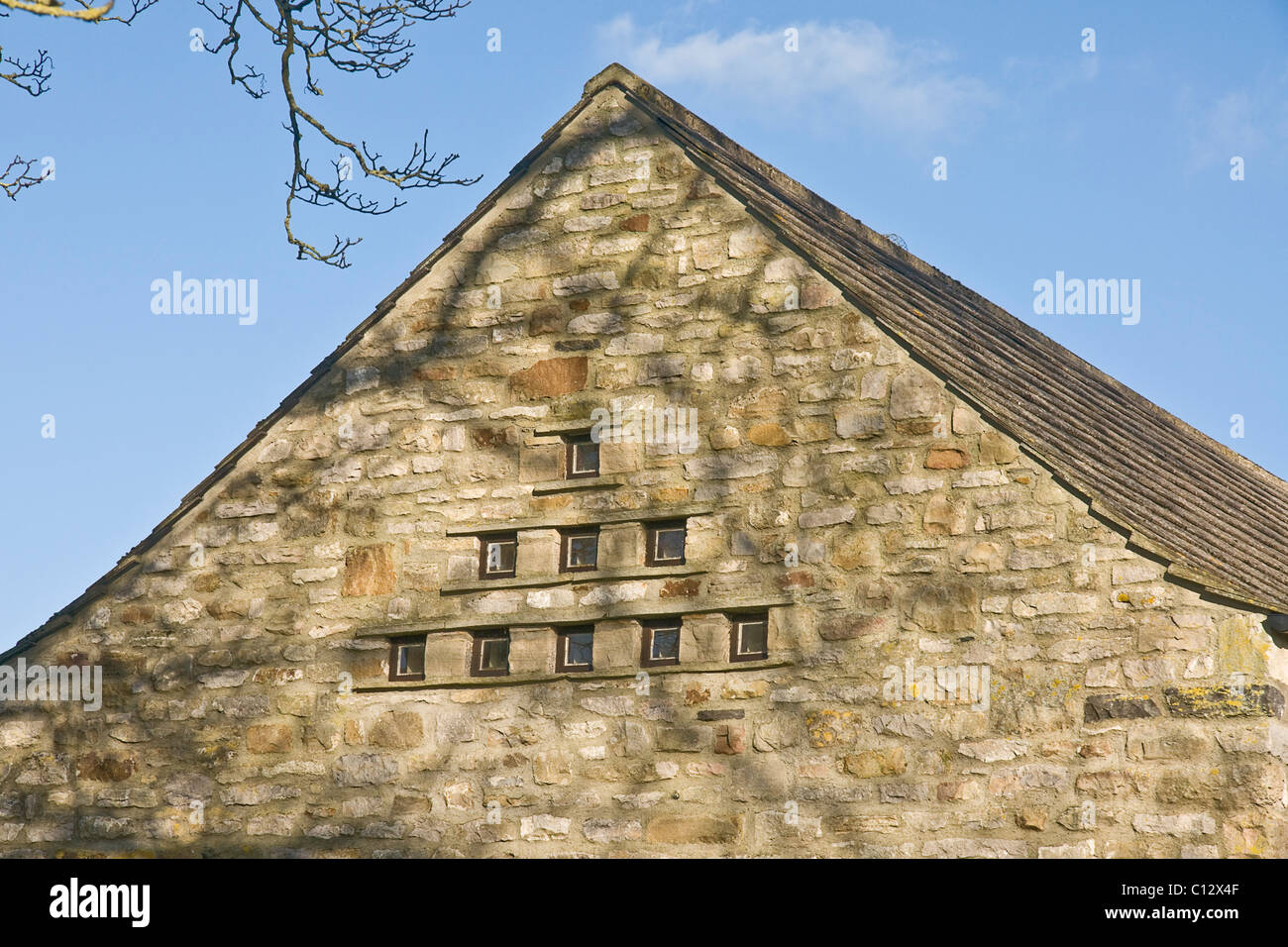 Feature window created from a dove cote in the gable wall of a barn conversion. - Stock Image