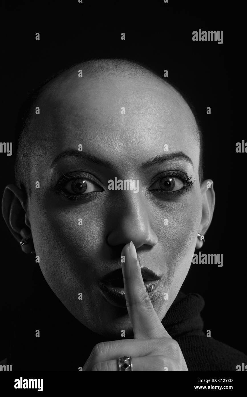 Portrait of a gay man with his finger on his lips - Stock Image