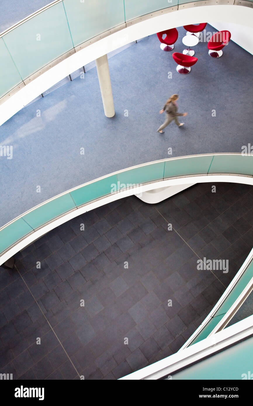 high angle view of woman walking in office building - Stock Image