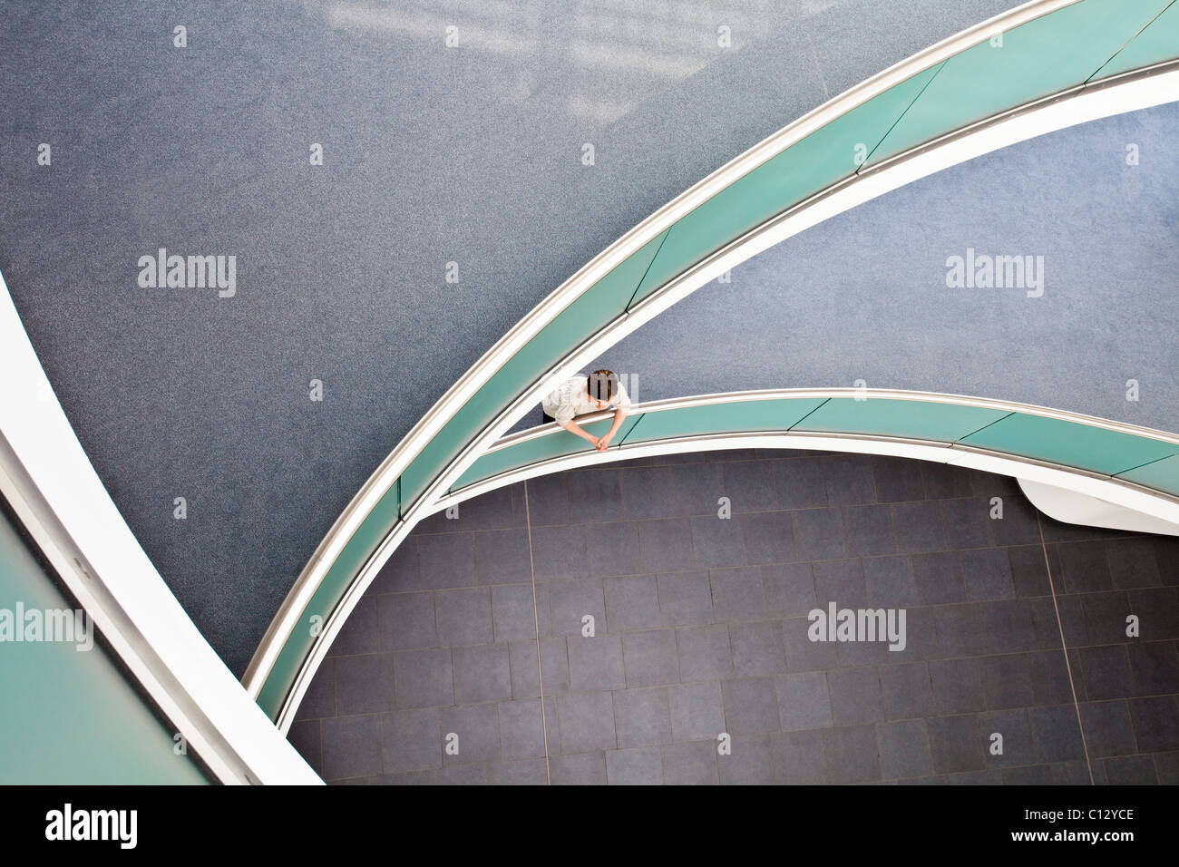 high angle view of woman standing in staircase of office building - Stock Image