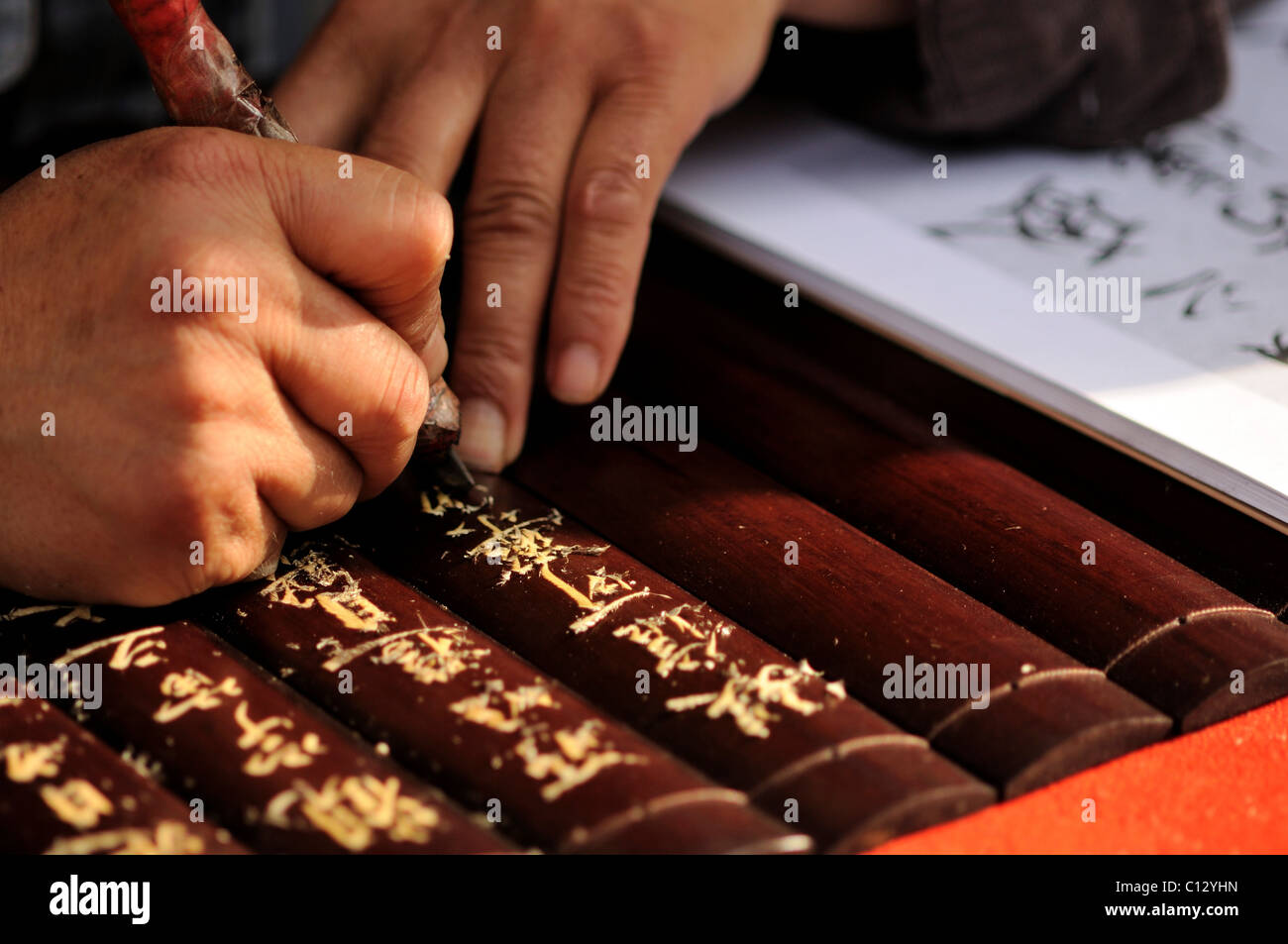 close-up of person carving chinese characters - Stock Image