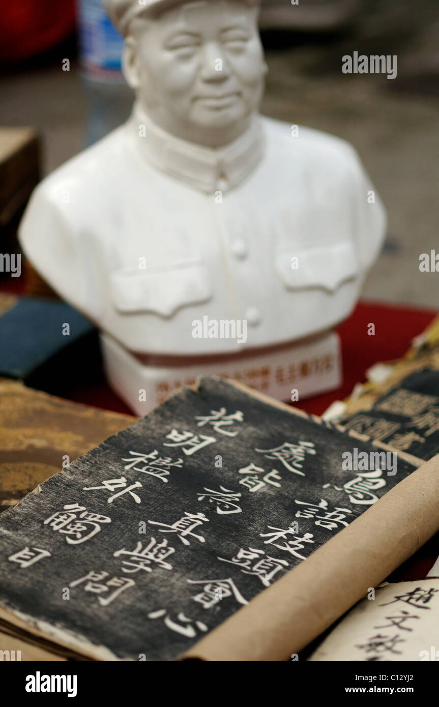 chinese book with sculpture of former chinese leader Mao Zedong in background - Stock Image