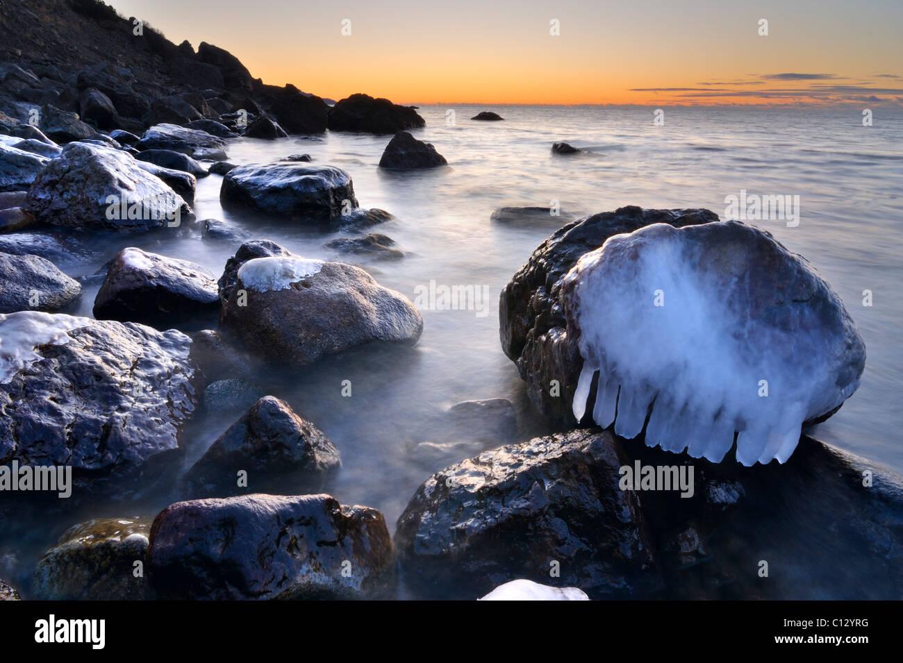 ice covered rocks on crimean black sea coast at robber bay - Stock Image