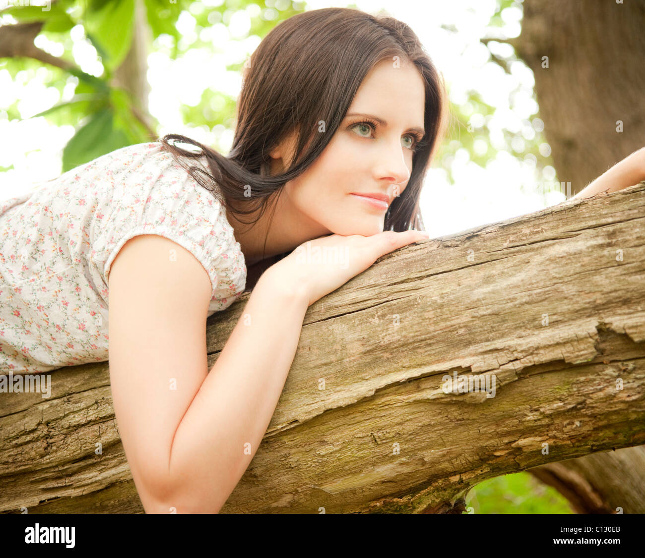 portrait of young woman lying on tree trunk - Stock Image